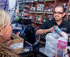 Prestonpans retailer Ferhan Ashiq serves a customer